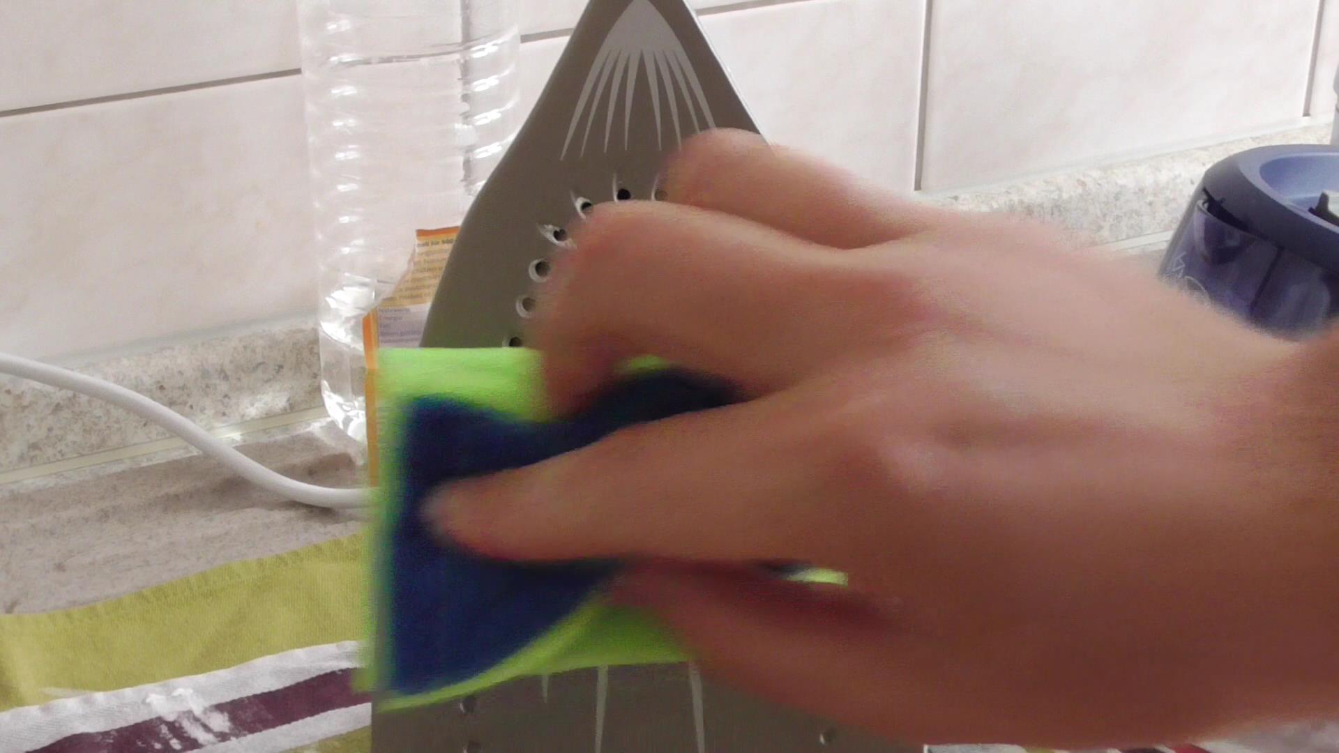 Abwischen der Bügelsohle mit einem Schwamm