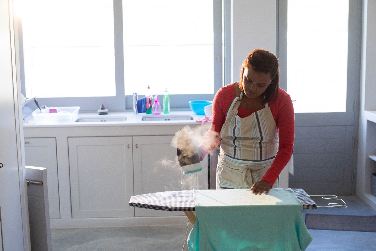 Frau bügelt mit Dampfbügeleisen